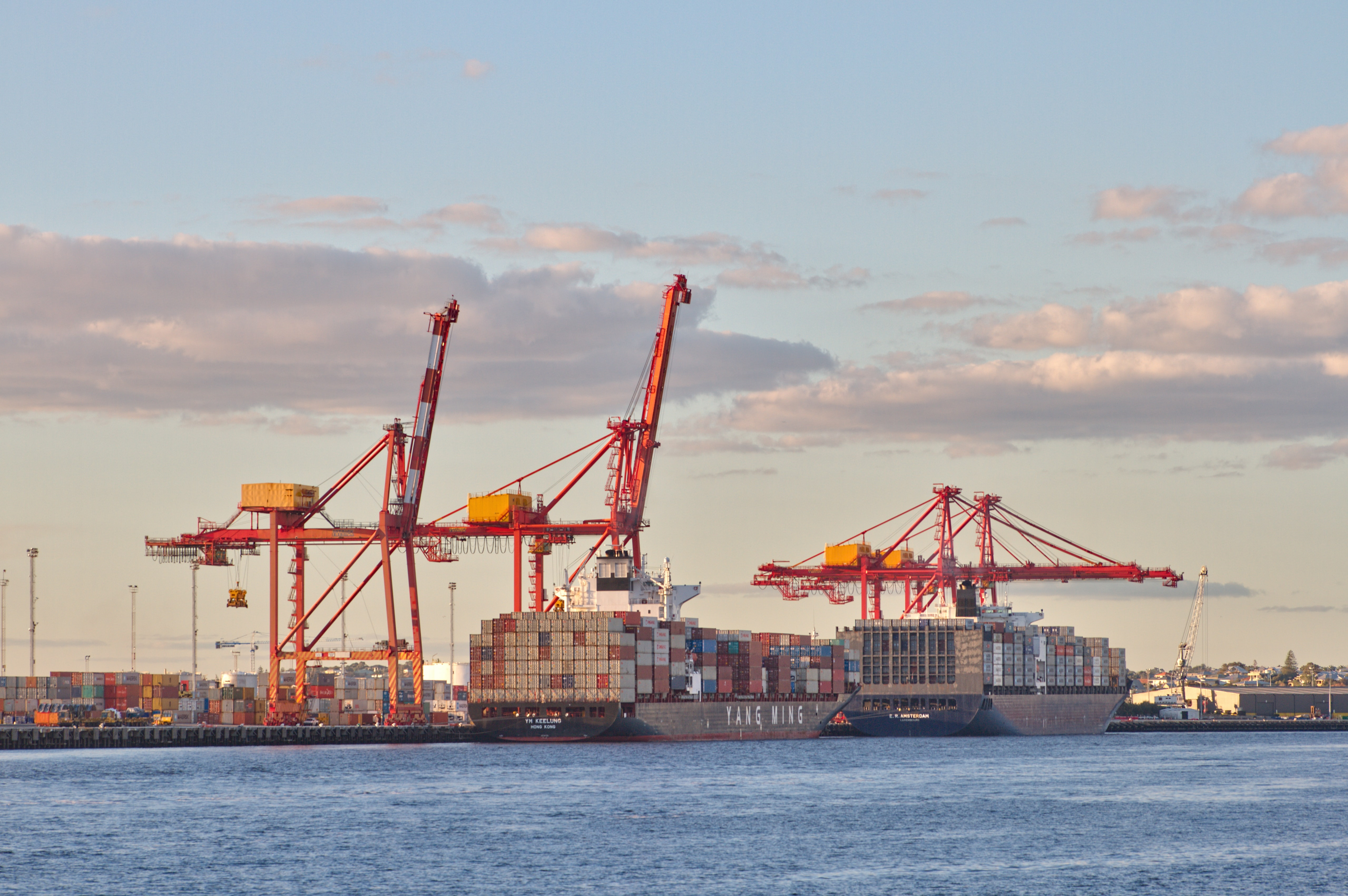 Image of several container ships filled with containers next to cranes ready for unloading